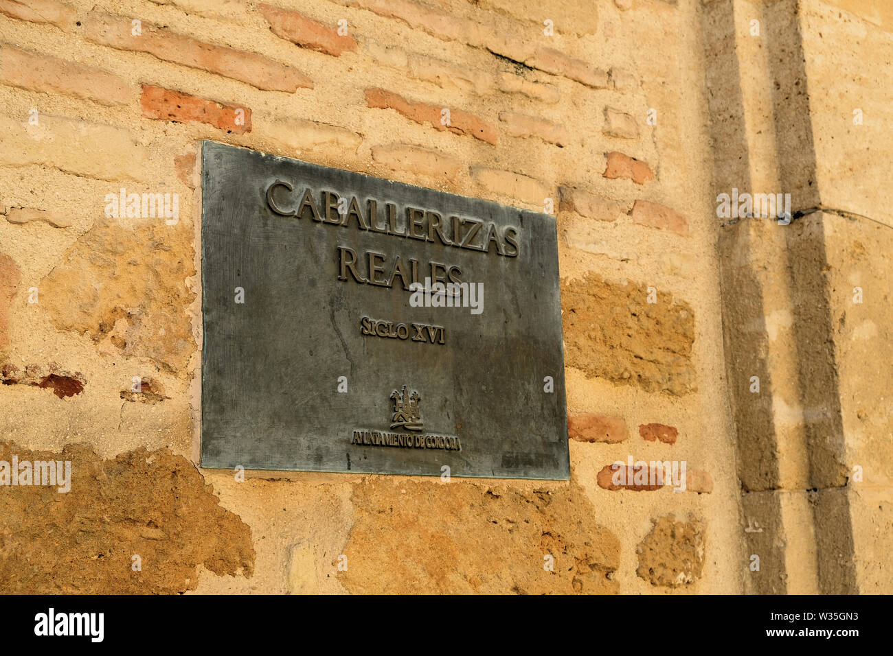Sign on a brick wall outside the royal stables or Caballerizas Reales in Cordoba, Andalusia, Spain indicating their 16th Century origin. - Stock Image