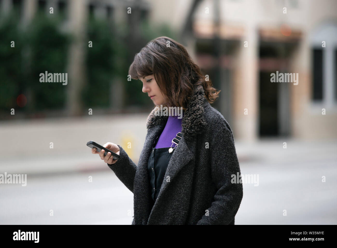 Young female using mobile phone app and waiting for a rideshare or pedestrian tourist checking online map for gps navigation.  Depicts city life and h Stock Photo