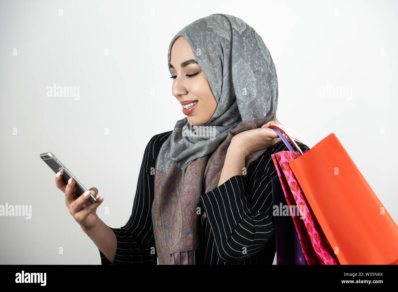 young beautiful smiling Muslim business woman wearing turban hijab headscarf tapping smartphone with one hand and carrying shopping bags in another - Stock Image