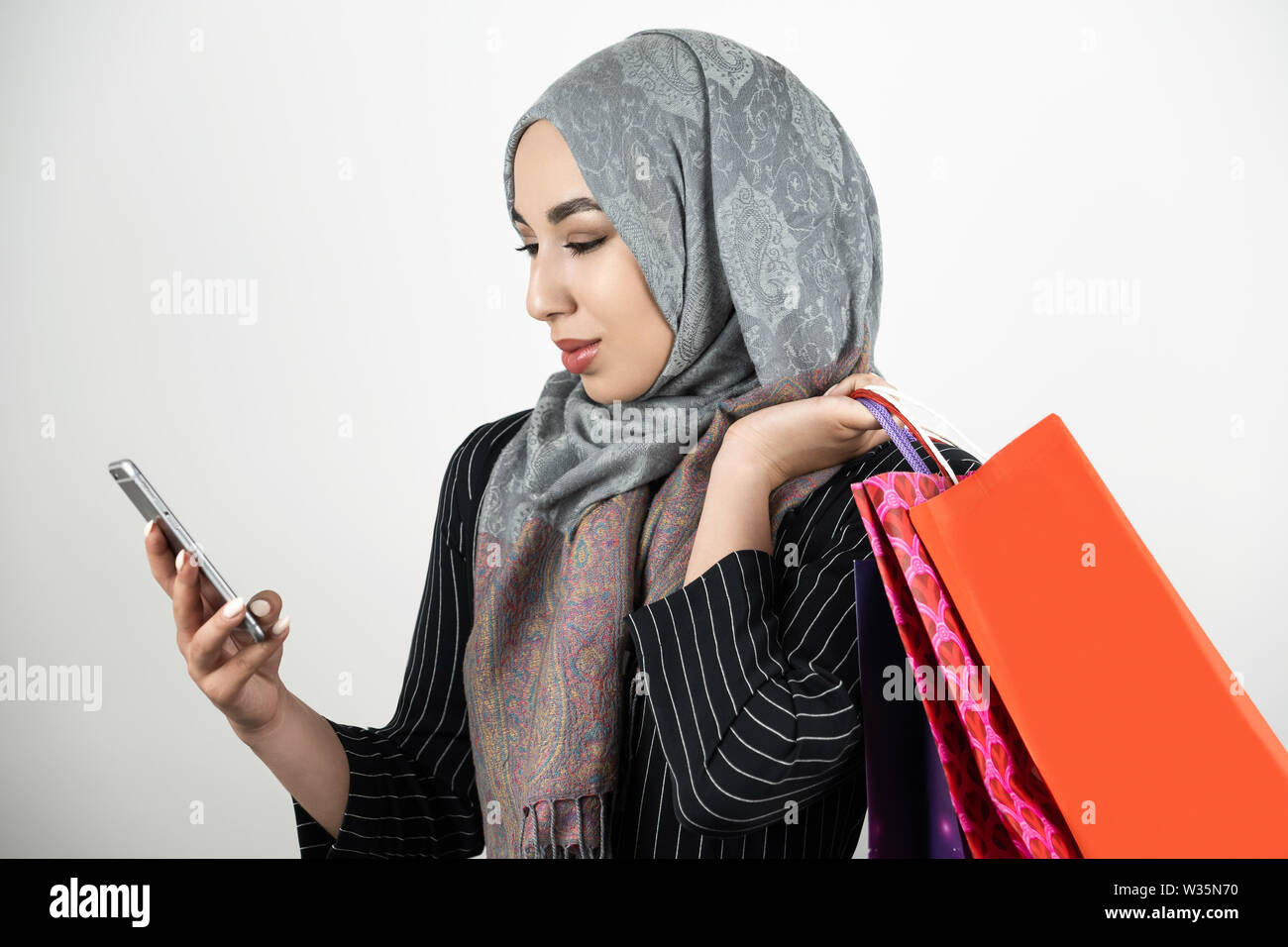 young beautiful Muslim business woman wearing turban hijab headscarf tapping smartphone with one hand and carrying shopping bags in another hand - Stock Image