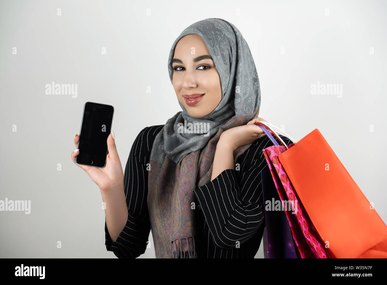 Muslim business woman wearing turban hijab headscarf showing smartphone with one hand and carrying shopping bags in another hand isolated white - Stock Image