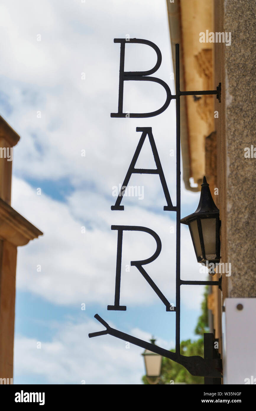 Metal sign with 'BAR' lettering on house facade, blue sky with white clouds and lanterns in the background (close-up, side view, vertical portrait ori - Stock Image
