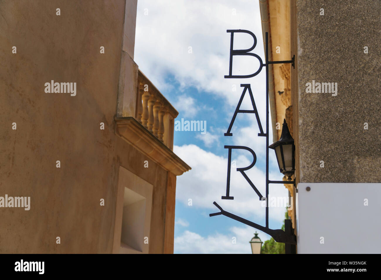 Metal sign with 'BAR' lettering on mediterranean house facade, blue sky with white clouds in the background (close-up, side view, horizontal landscape - Stock Image