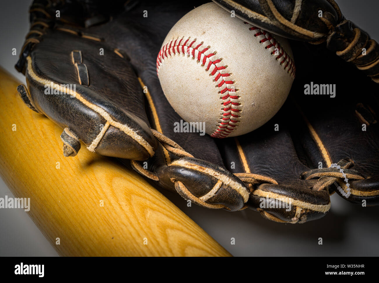 A black leather glove with baseball and bat over white background Stock Photo
