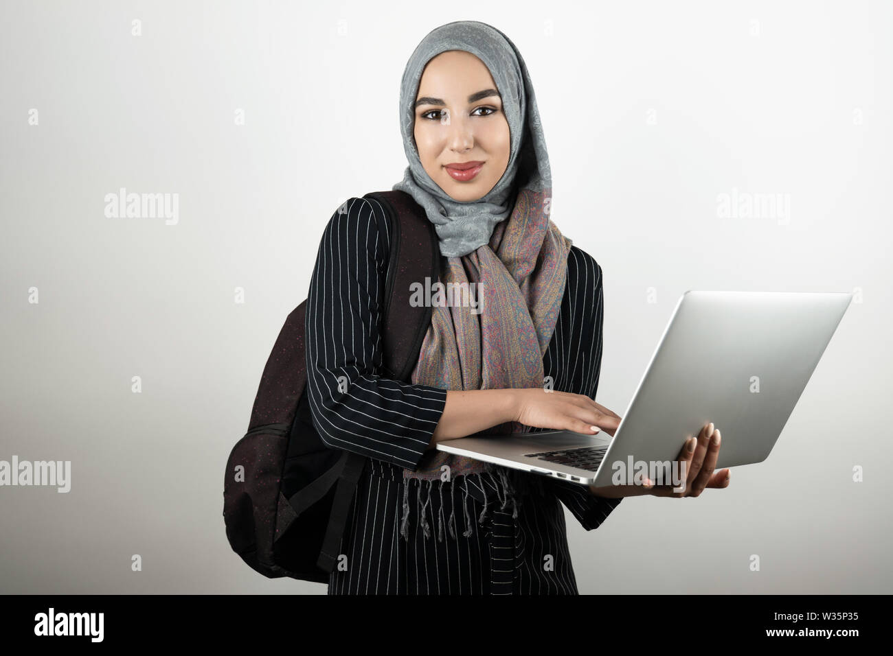 young attractive Muslim student with bagpack holding and tapping her laptop wearing turban hijab headscarf isolated white background - Stock Image