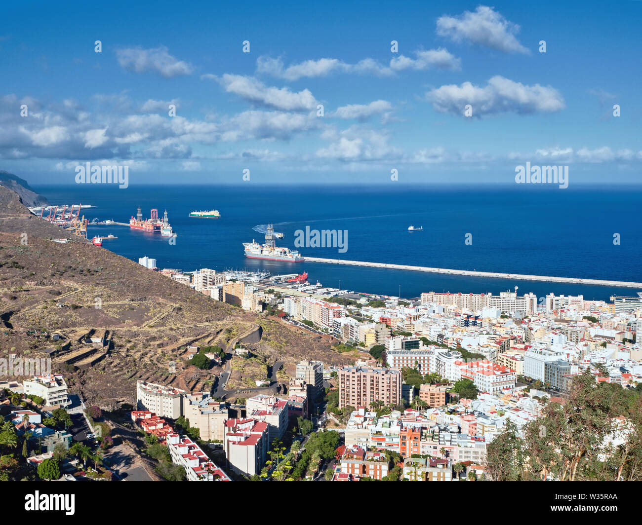 Port entrance of Santa Cruz de Tenerife photographed from high above. Dark blue Atlantic Ocean and sky with white clouds, a partial view of the white - Stock Image