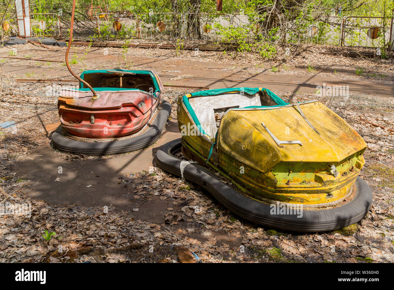 Old broken rusty metal radioactive children's electric cars  abandoned, the park of culture and recreation in the city of Pripyat, the Chernobyl disas - Stock Image