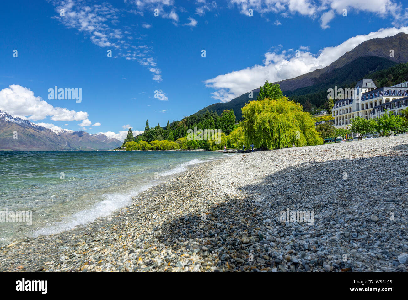Stoney shoreline of Lake Wakatipu with mountains in background, Queenstown, South Island New Zealand Stock Photo