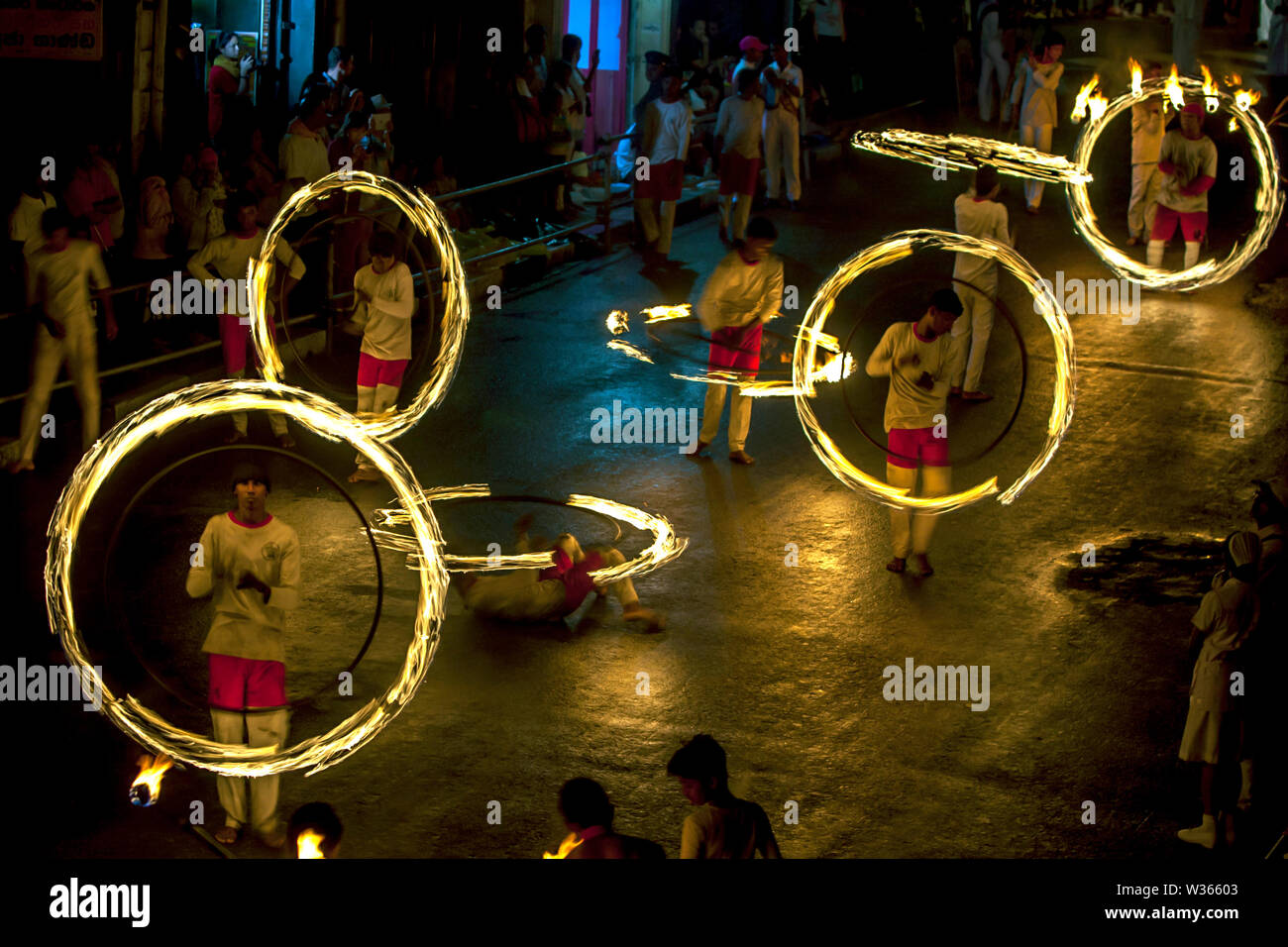 A spectacular site as Fire Ball Dancers perform along Colombo Street in Kandy during the Buddhist Esala Perahera (procession) in Sri Lanka. - Stock Image