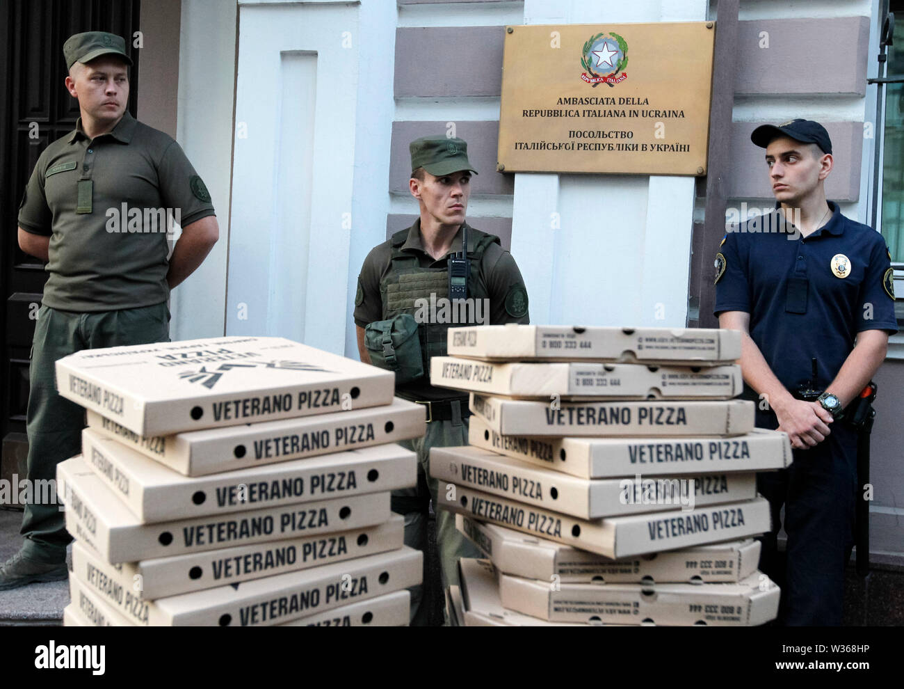 Kiev, Ukraine. 12th July, 2019. Police officers stand next to a barricade of pizza boxes placed by activists during a rally demanding the release of Ukrainian serviceman Vitaly Markiv, outside the Embassy of Italy in Kiev, Ukraine. An Italian court has sentenced Ukrainian former National Guard commander, Vitaliy Markiv to 24 years in prison for the murder of a photographer Andrea Rocchelli and his Russian translator and assistant Andrei Mironov in the early days of the war conflict in the East of Ukraine in May 2014, between government forces and pro-Russian separatists. Credit: SOPA Images Li - Stock Image