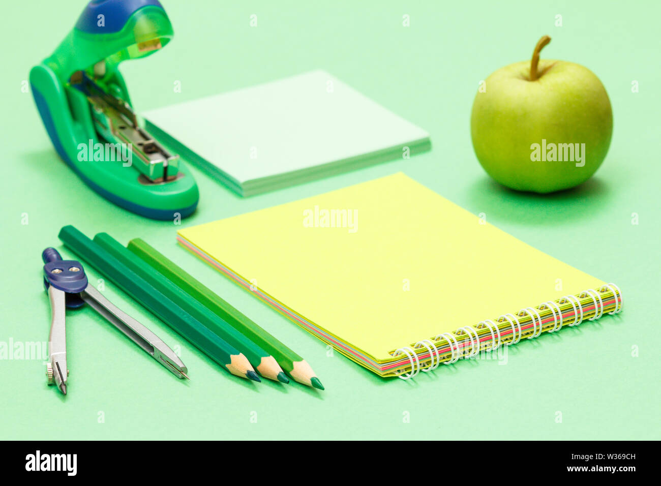 Compass, color pencils, notebook, apple, note paper and stapler on green background. Back to school concept. School supplies. Shallow depth of field. - Stock Image