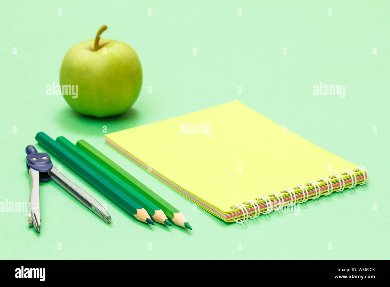 Compass, color pencils, notebook and apple on the green background. Back to school concept. School supplies. Shallow depth of field. - Stock Image