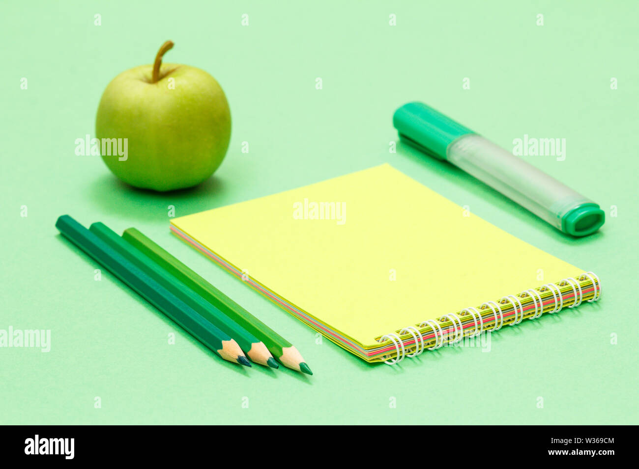 Color pencils, notebook, felt pen and apple on green background. Back to school concept. School supplies. Shallow depth of field. - Stock Image