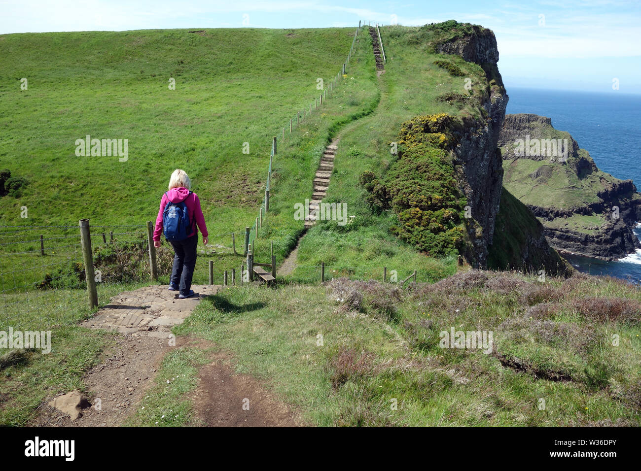 Woman Walking Towards Steps on the Giant's Causeway Coastal Path, County Antrim, Northern Ireland, UK Stock Photo