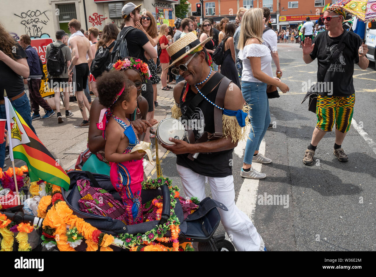 St Pauls, Bristol, UK. July 6th 2019. The 51st St Pauls Carnival Procession wound its way through Bristols St Pauls on a hot and sunny Saturday afternoon. The carnival attracted around 100,000 people. Organised by the St Pauls Carnival Community Interest Company. Pictured, young child encouraged by mother to tap drum belonging to procession participant. Credit: Stephen Bell/Alamy - Stock Image