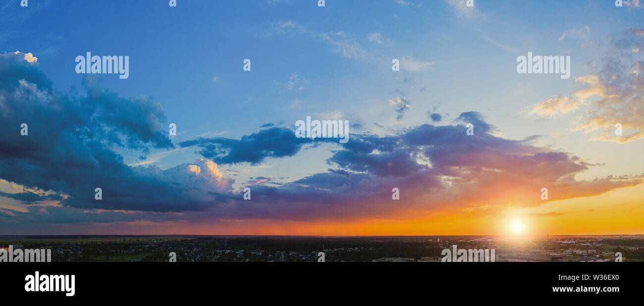 Panorama of the evening sky at sunset with beautiful cumulus clouds above the city - Stock Image