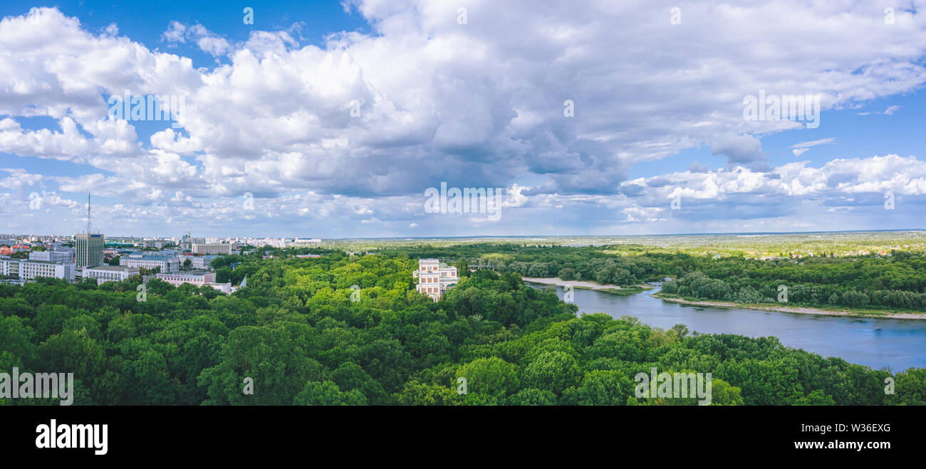 Panorama of the city park under beautiful cumulus clouds. River and trees within the city in Belarus - Stock Image