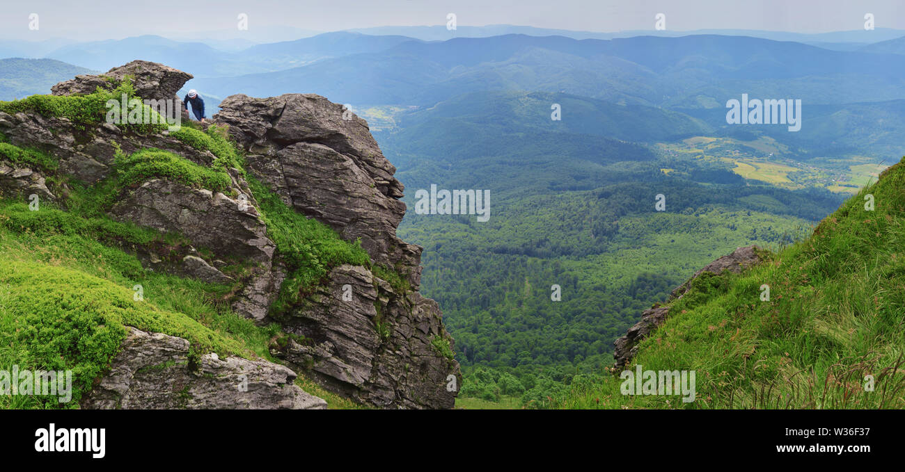 One man in a hat climbing on rocks on Pikuy mount against the valley among majestic green mountain hills covered in lush grass and forest. Cloudy summ Stock Photo
