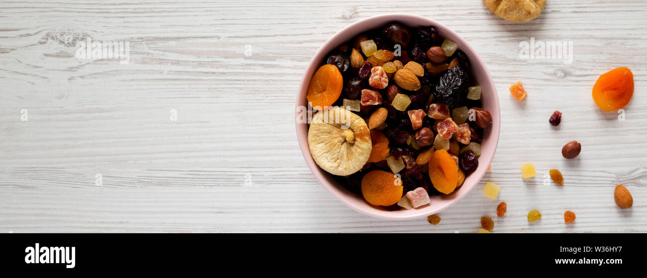 Dried fruits and nut mix in a pink bowl on a white wooden surface, top view. Overhead, from above, flat lay. Copy space. Stock Photo
