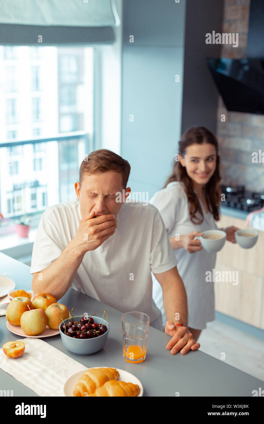 Dark-haired sleepy husband waiting for coffee in the morning - Stock Image