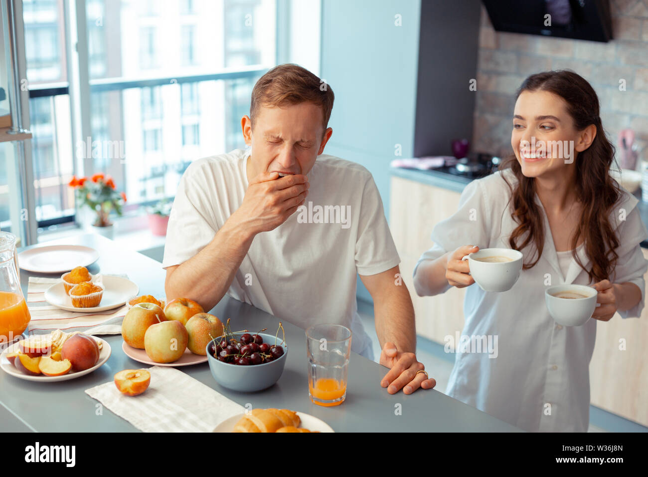 Smiling wife bringing some coffee for sleepy husband - Stock Image