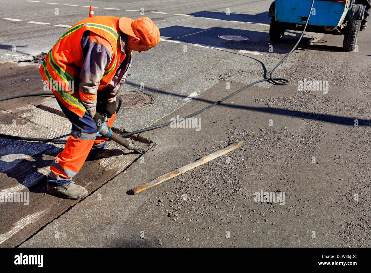 A road maintenance worker removes old asphalt with a pneumatic jackhammer during road construction. - Stock Image