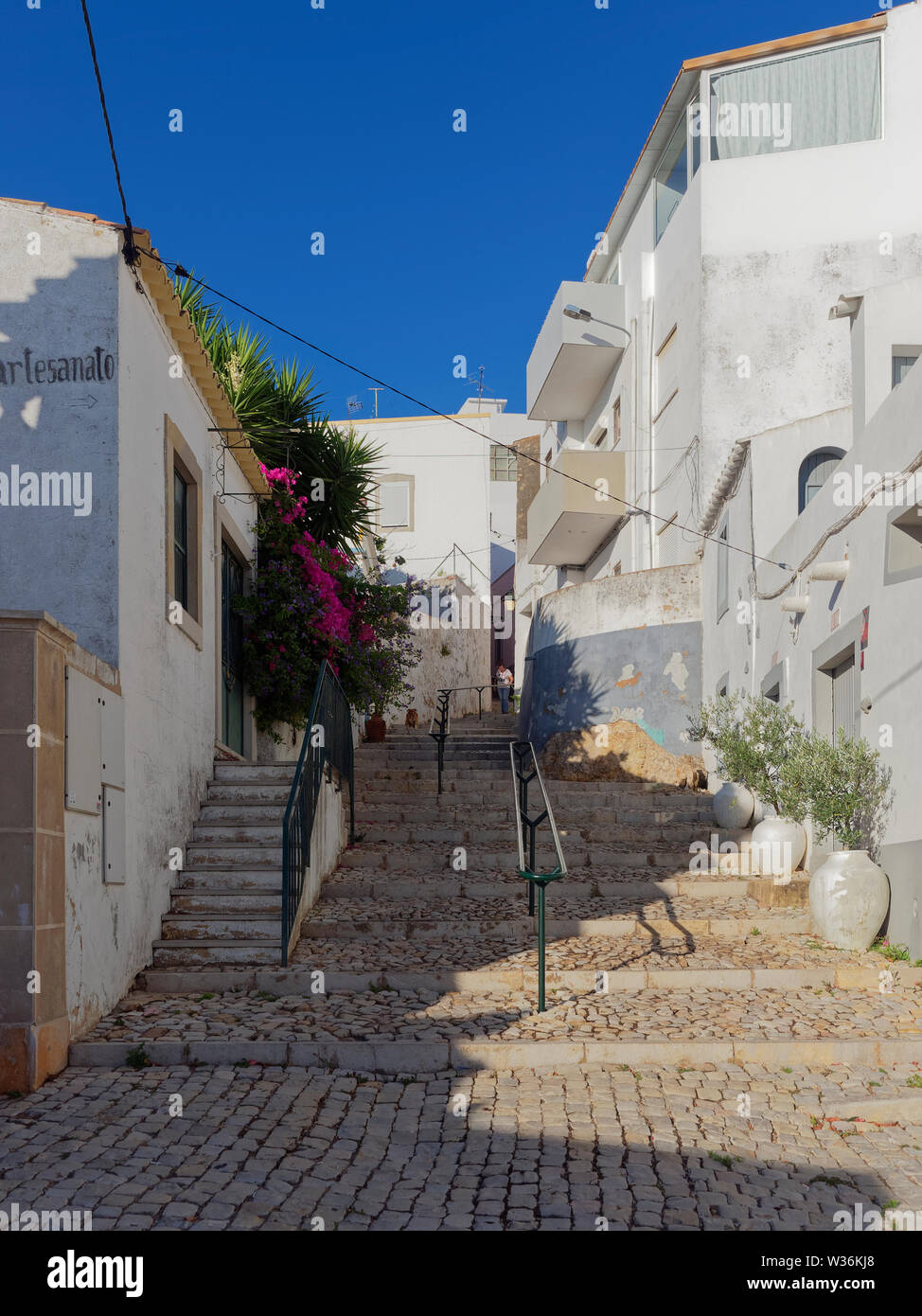 Looking up an old Cobbled street with stone steps and hand rails with a Person walking down between the terraced Houses. Estoi, Portugal. Stock Photo