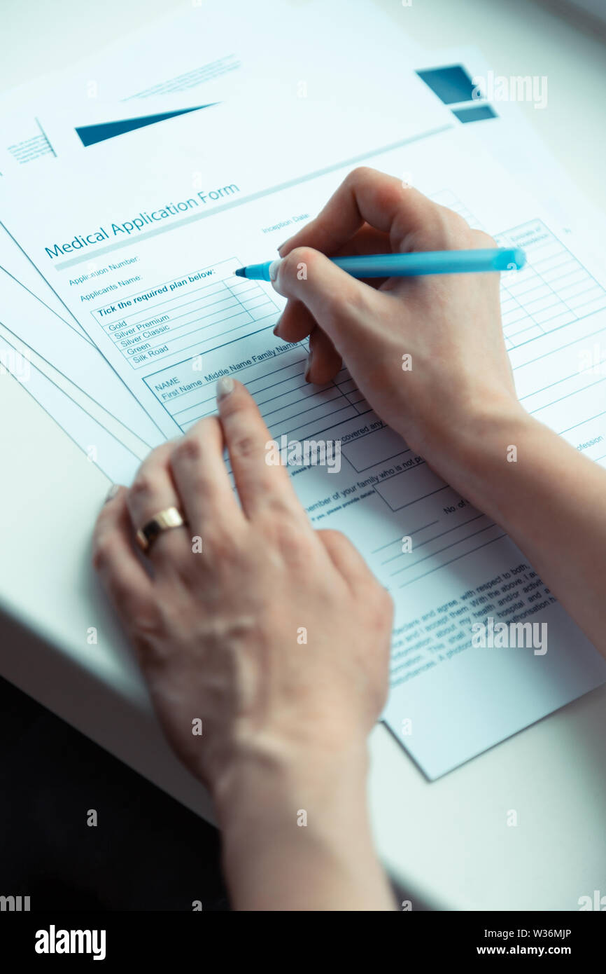Woman holding pen and signing papers buying medical insurance Stock Photo
