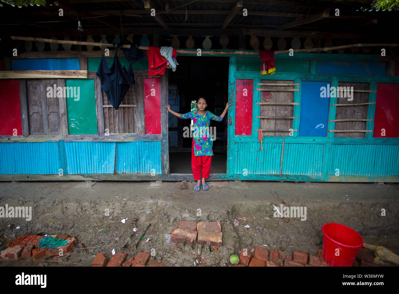 Bangladesh – June 27, 2015: A girl is standing at their door whose house was destroyed of massive river erosion at Rasulpur, Barisal District. - Stock Image