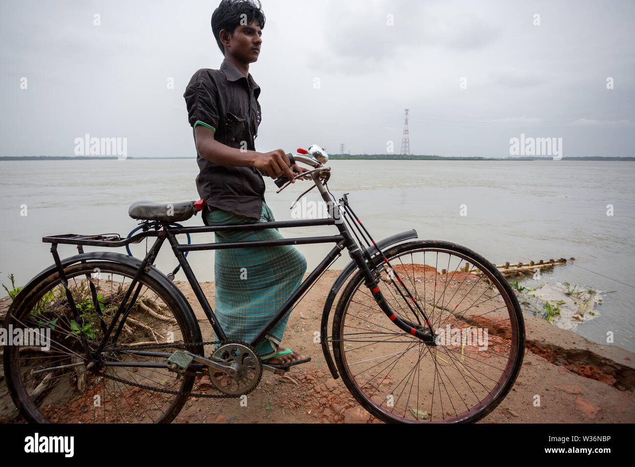 Bangladesh – June 27, 2015: A bicycle boy are stuck on the way due to river erosion at Rasulpur, Barisal District. - Stock Image