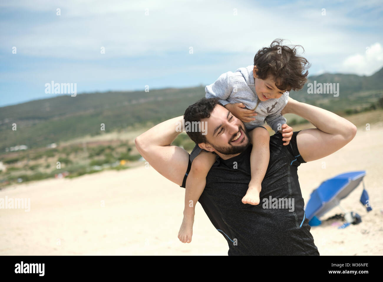 father playing with son in Bolonia beach Stock Photo