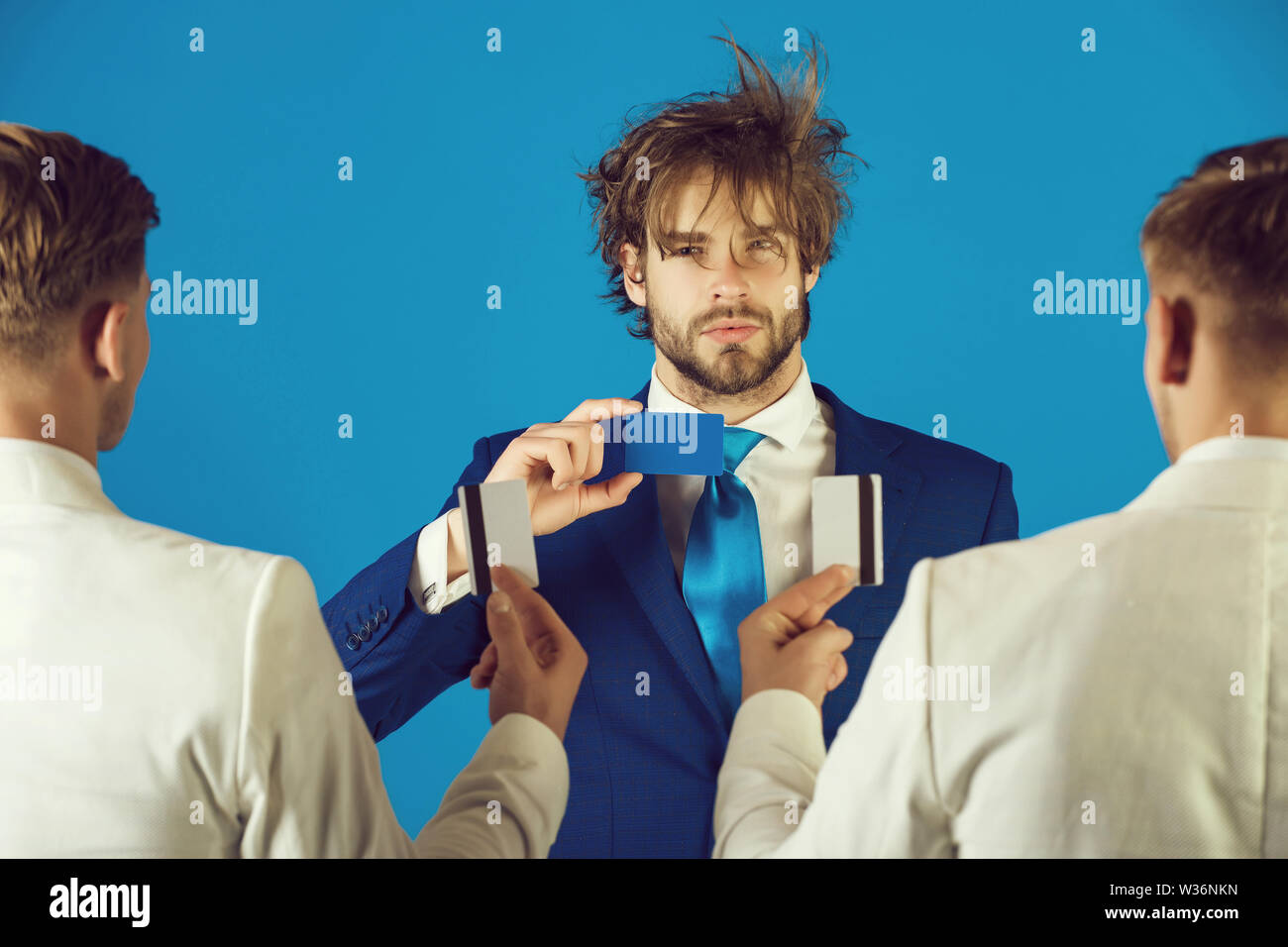 Men wearing white jackets, back view. Information and cooperation. Business ethics concept. Businessmen exchanging cards on blue background. Group of - Stock Image
