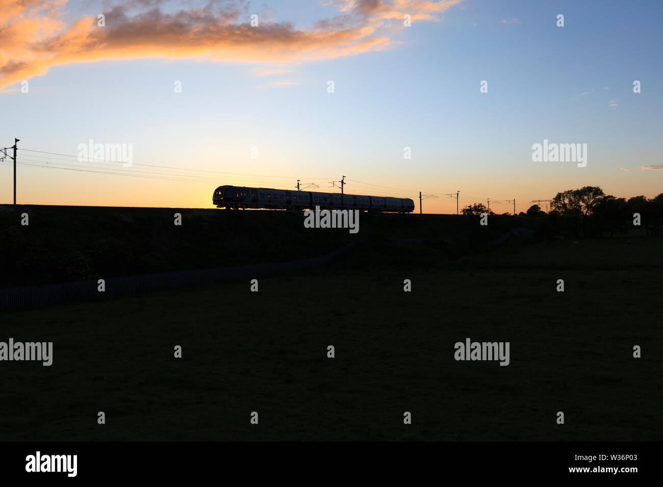 New CAF class 195 train for Arriva Northern Rail making a silhouette at sunset on the west coast main line while on a driver training run Stock Photo
