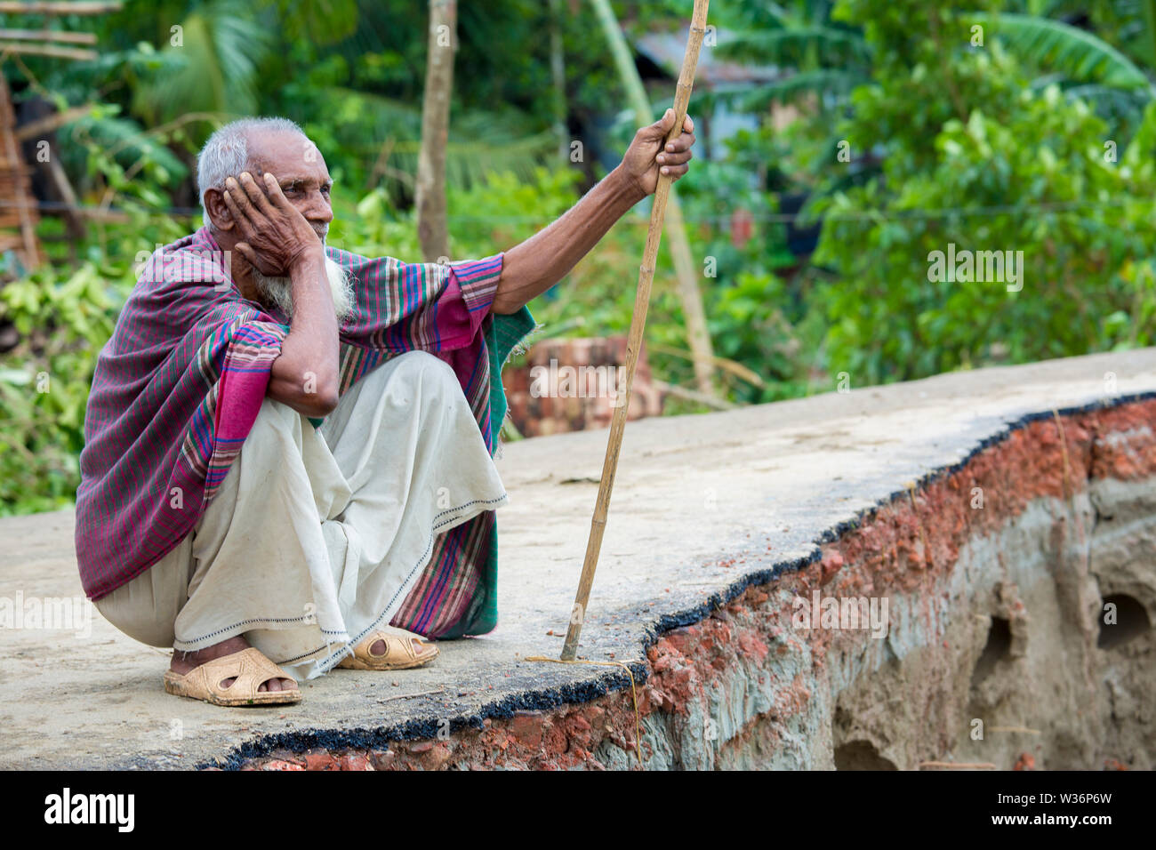 Bangladesh – June 27, 2015: An old man is showing where is his previous house was at Rasulpur, Barisal District. - Stock Image
