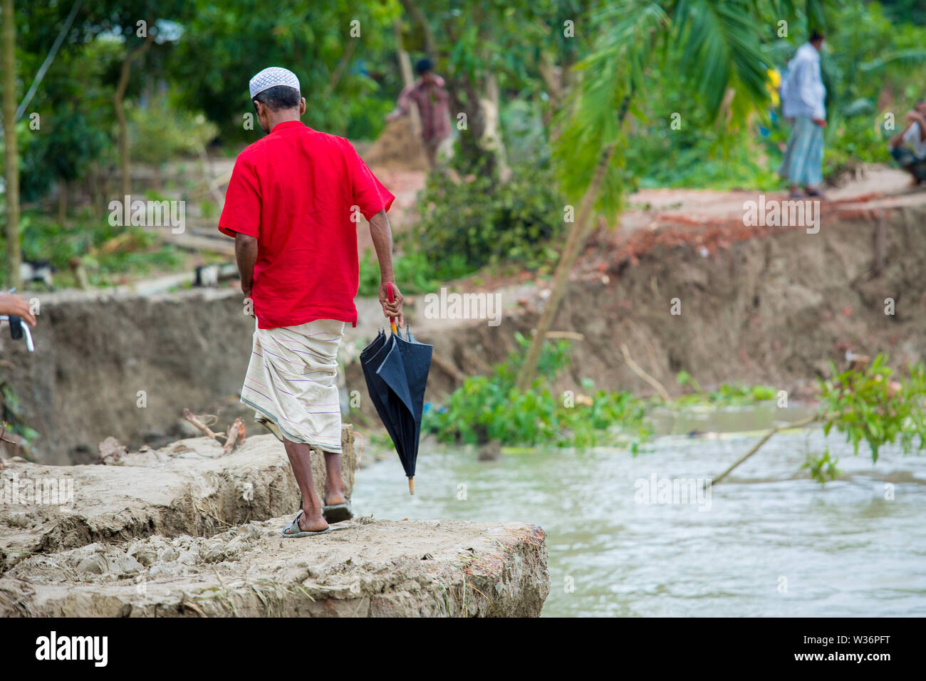 Bangladesh – June 27, 2015: Man woman and peoples are crossing river erosion affected roadside at Rasulpur, Barisal District. - Stock Image
