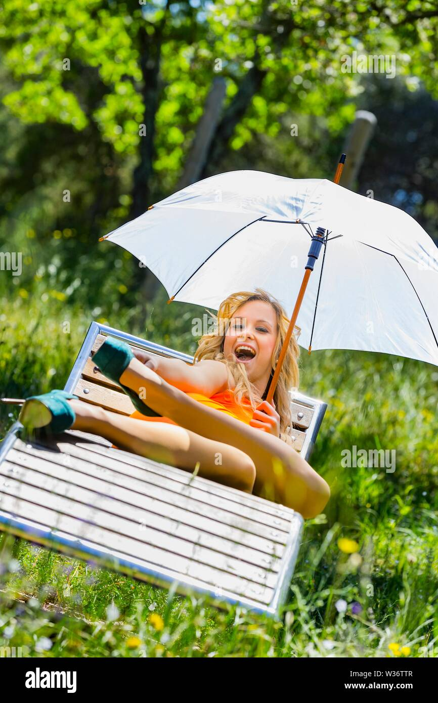 Attractive female person legs in heels lying on deckchair deck-chair in Green forest natural environment nature laughing loudly looking at camera MR Stock Photo