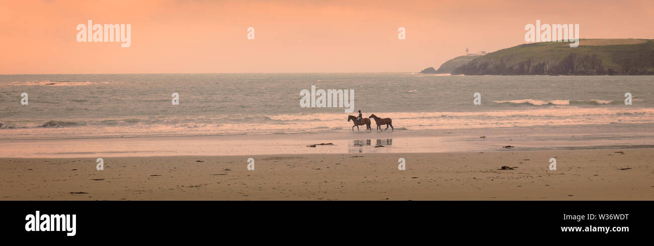 Horse rider leading second horse in the shallows of Owenahincha Beach near Rosscarbery, County Cork, Republic of Ireland. Eire. Galley Head lighthouse Stock Photo