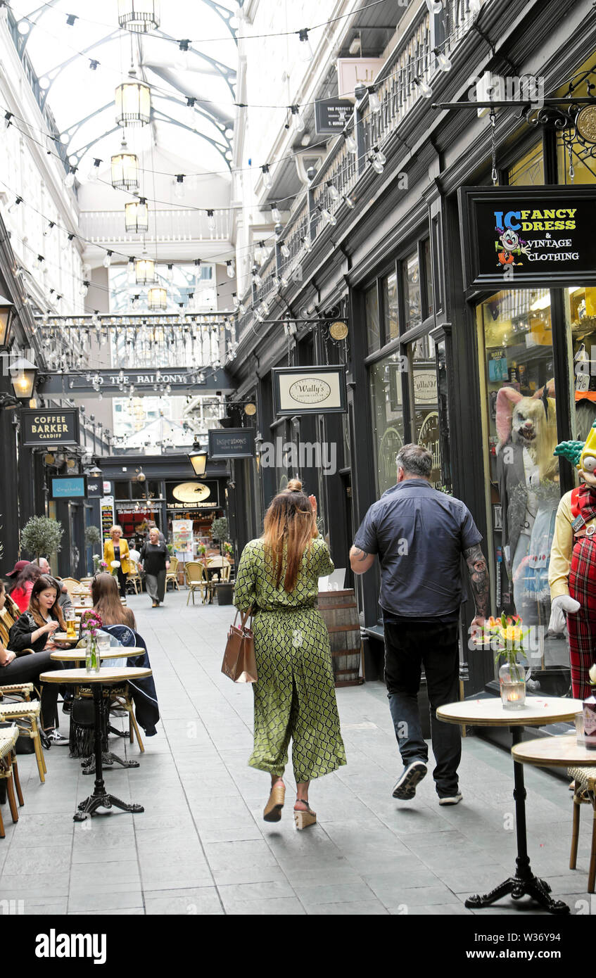 People shoppers walking , sitting, eating, drinking coffee in Castle Arcade covered shopping area in Cardiff Wales UK  KATHY DEWITT Stock Photo