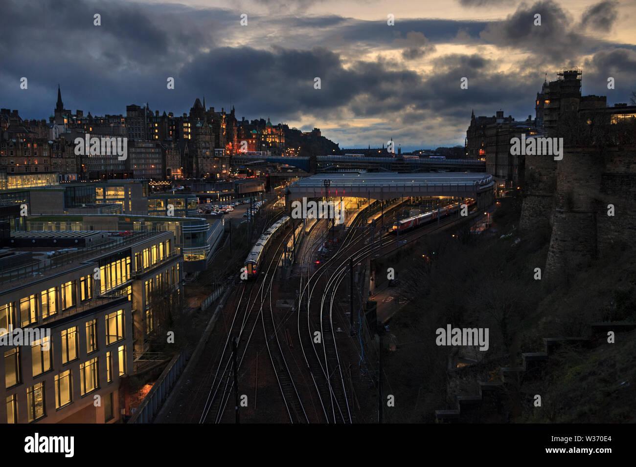 A Abellio Scotrail class 380 train arriving at  Edinburgh Waverley stations east end  at sunset with the Edinburgh skyline Stock Photo