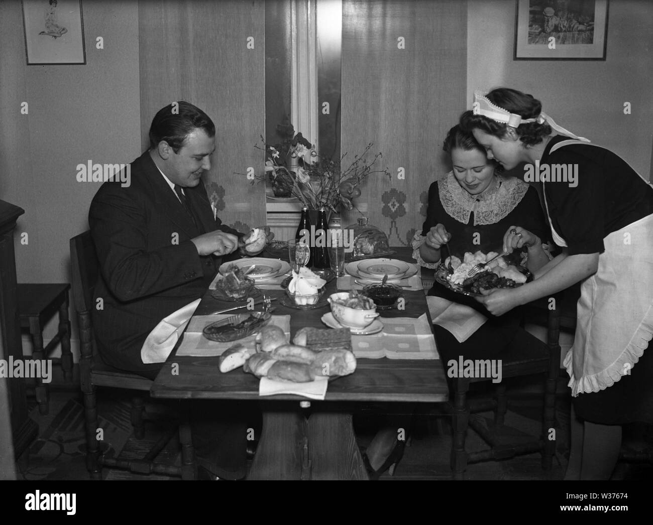 Living in the 1940s. A young woman working as a maid is serving dinner to a man and woman sitting at the table. She is neatly dressed in a white apron.   Sweden 1940. Kristoffersson ref 55-7 - Stock Image