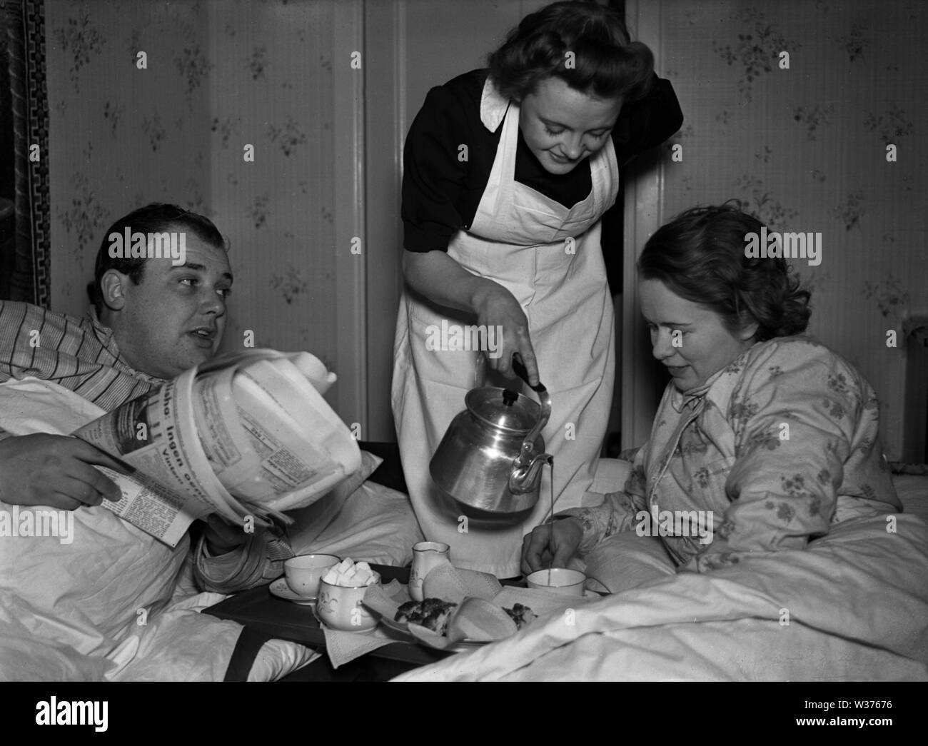 Living in the 1940s. A young woman working as a maid is serving morning coffee to mr and mrs while they still are in bed. She is neatly dressed in a white apron.   Sweden 1940. Kristoffersson ref 55-8 - Stock Image