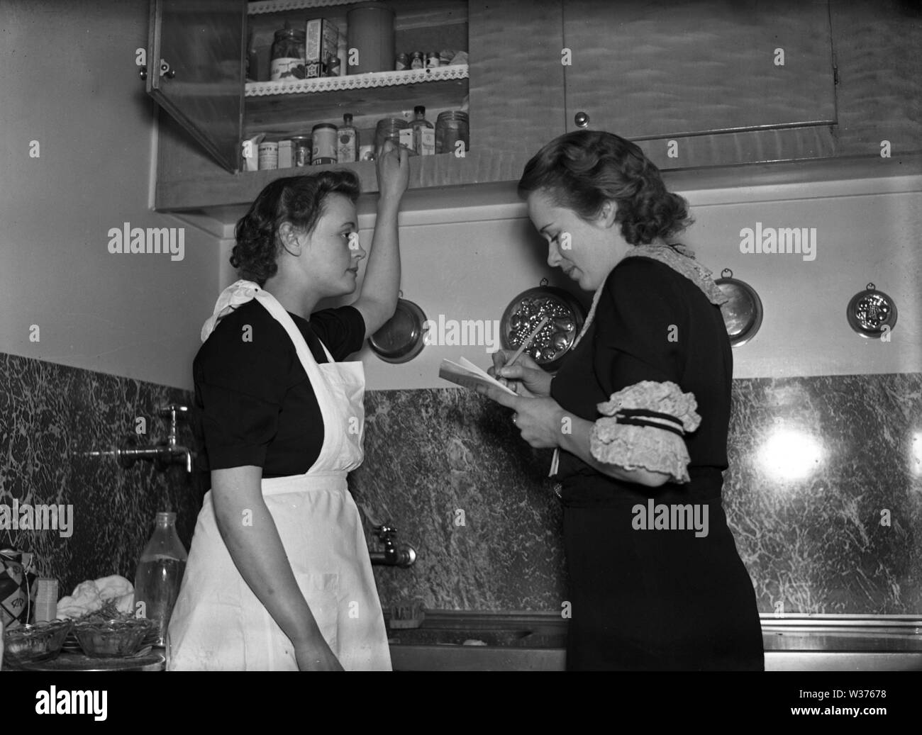 Living in the 1940s. A young woman working as a maid with the housewife  who writes a list of things to do and what to buy. Sweden 1940. Kristoffersson ref 55-6 - Stock Image
