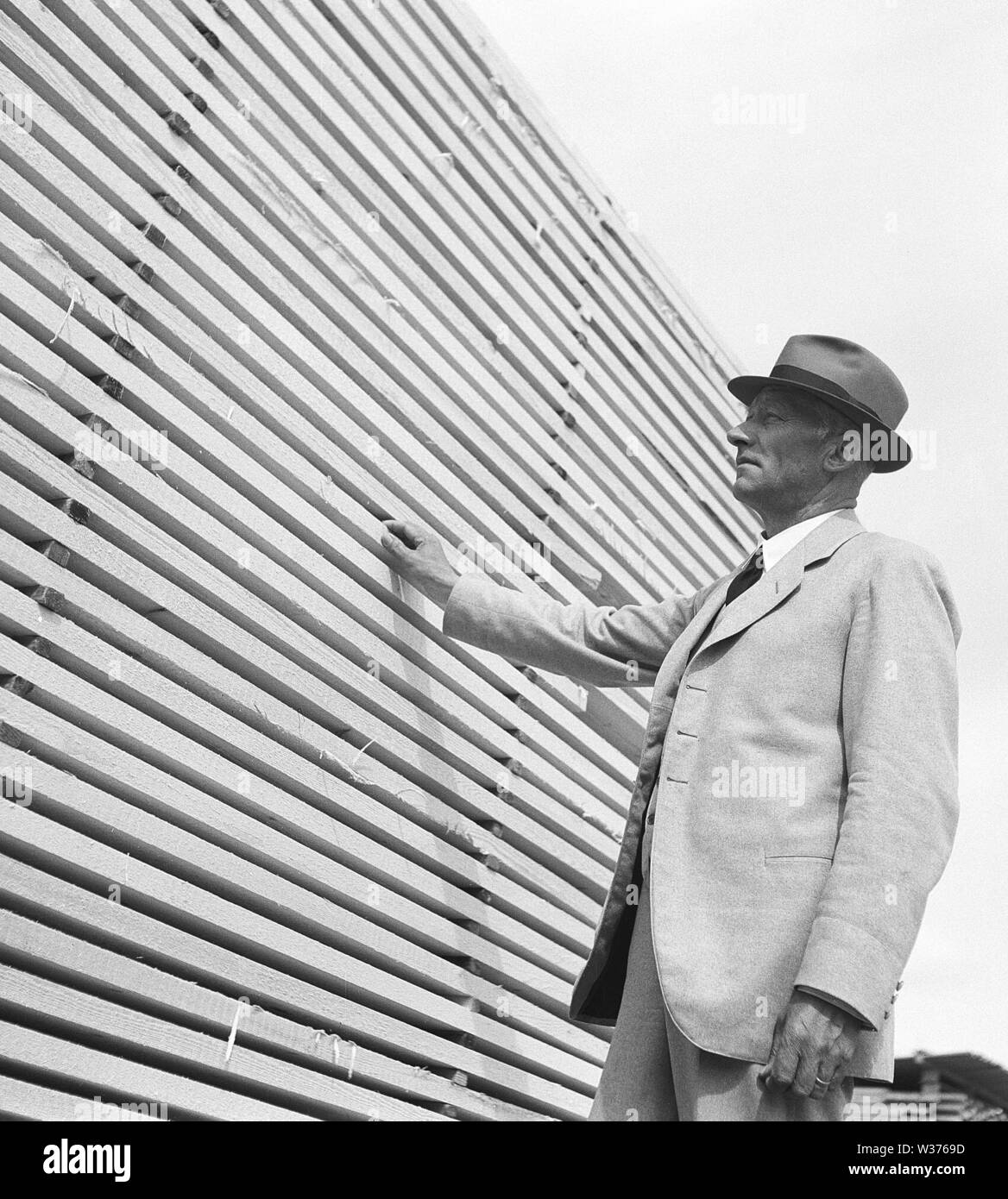 Stacks of wood boards stored correctly at a sawmill. A director is having a look that the quality is right. Sweden 1940. Kristoffersson ref 205-9 - Stock Image