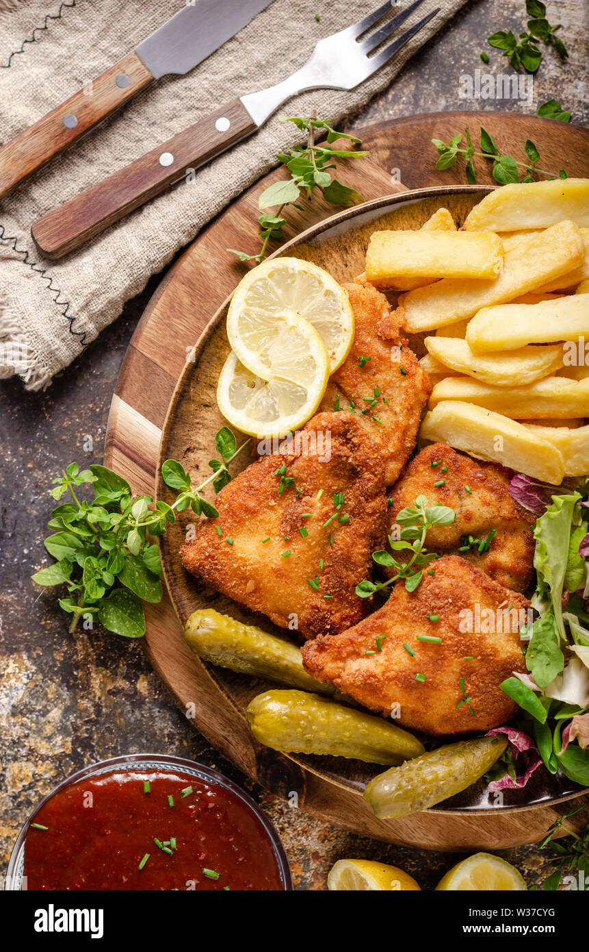 Delicious breaded meat with french fries, salad, pickless and beer - Stock Image
