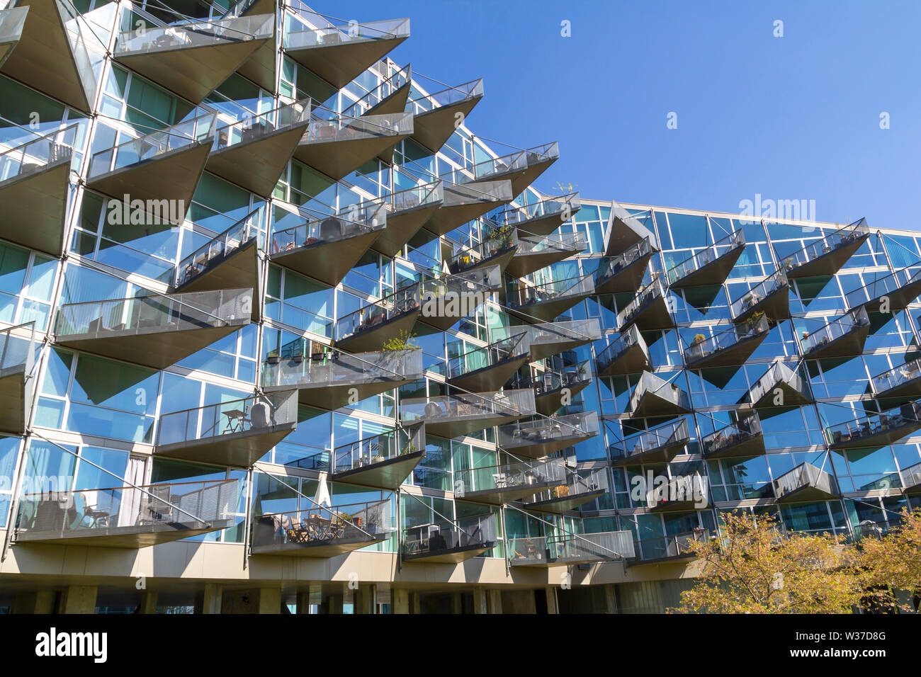 Modern architecture building in Orestad, Copenhagen, with triangular balconies in a glass facade Stock Photo