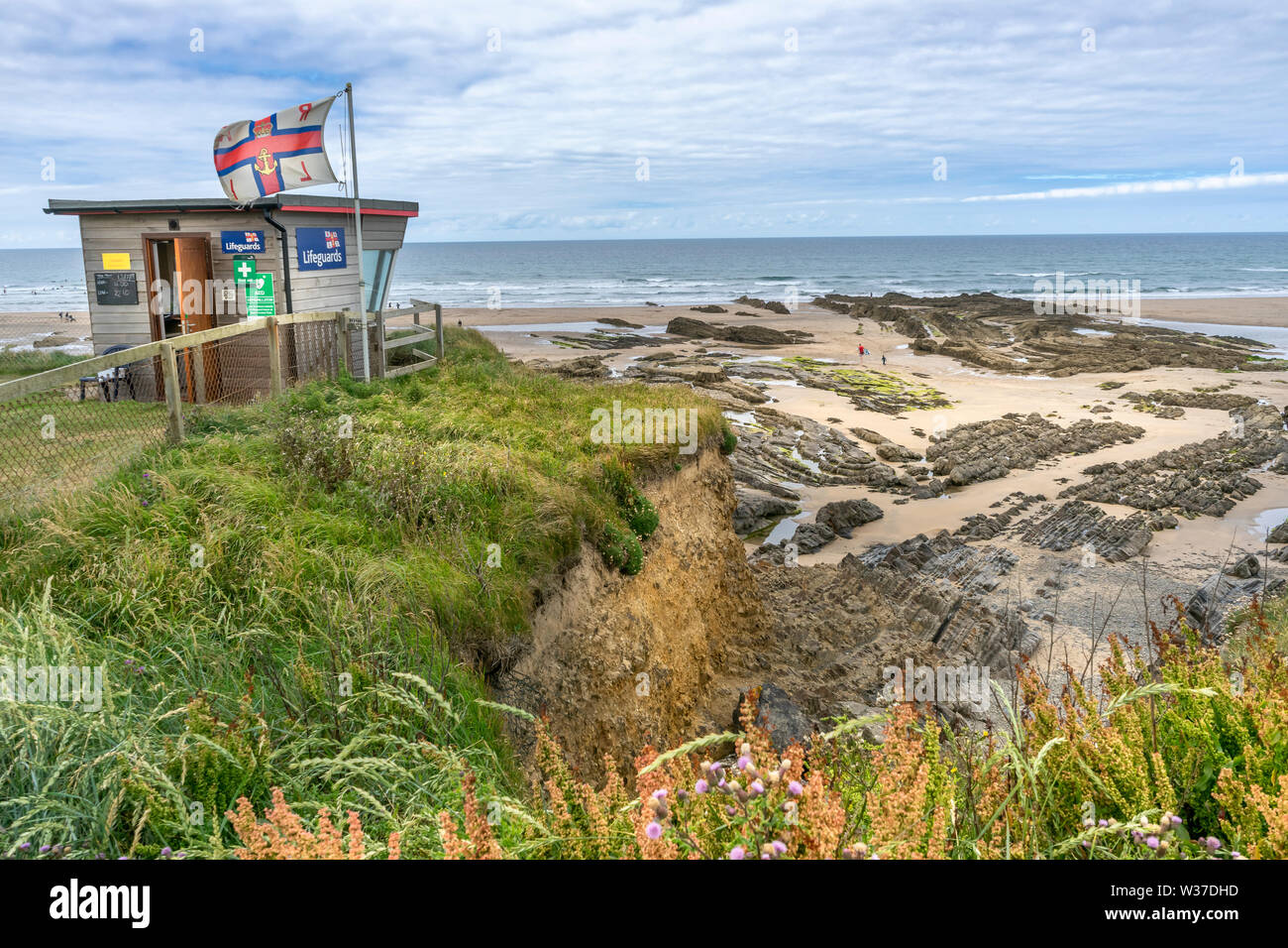Bude Beach, North Cornwall, England. Saturday 13th July 2019. UK Weather. Lower temperatures, overcast skies and a cooling breeze on the North Cornish coast as Bude still welcomes holidaymakers to the popular coastal resort in North Cornwall. Stock Photo