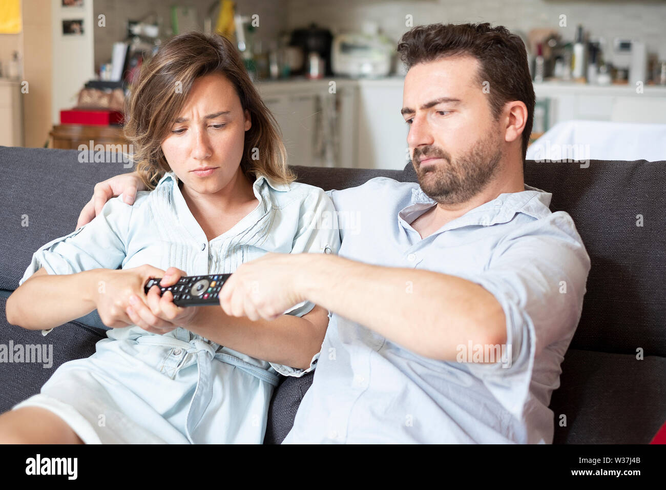 Angry couple fighting for the remote control - Stock Image
