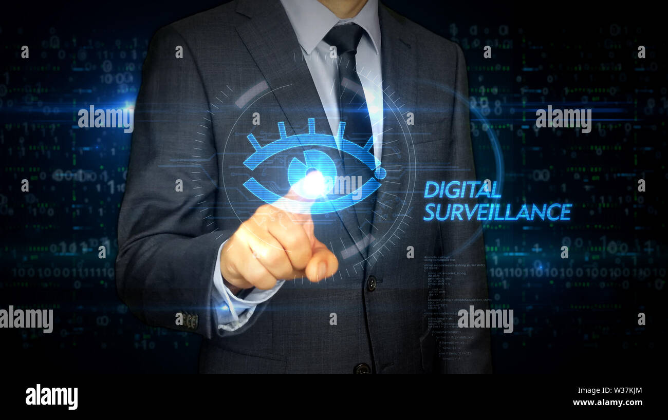 A businessman in a suit and screen with cyber eye hologram. Man using hand on virtual display interface. Digital surveillance, spying, hacking and vio Stock Photo