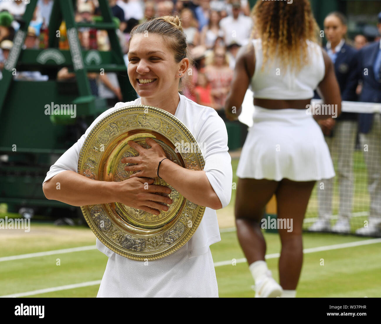 London, UK. 13th July, 2019. The Championships Wimbledon 2019 13072019 Simona Halep hugs winners trophy the Venus rosewater Dish after she wins Ladies Singles Final, and her beaten opponent Serena Williams leaves centre court. Credit: Roger Parker/Alamy Live News - Stock Image