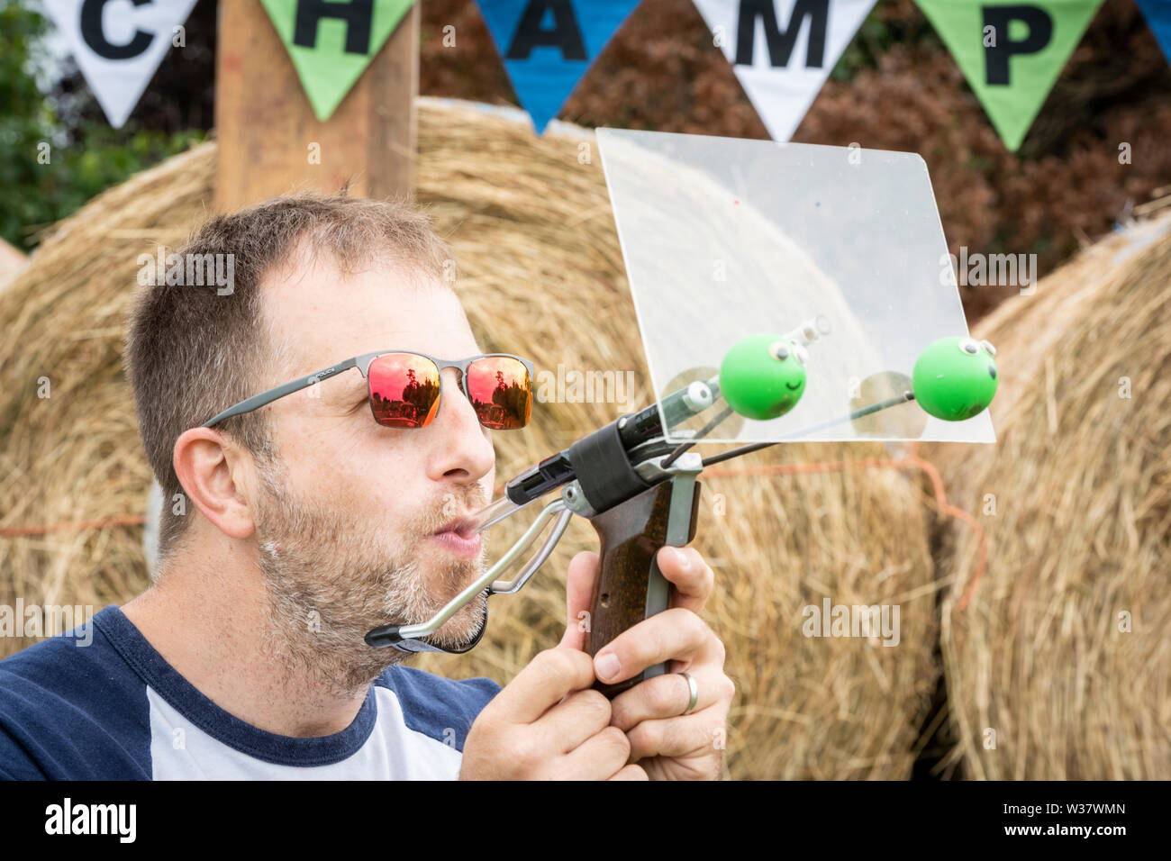 Witcham, near Ely, Cambridgeshire UK. 13th July 2019. Rob Bresler, a former champion, shoots at the 49th World Pea Shooting Championship. The annual event, held since 1971 raises funds for the village hall and attracts competitors who use a mixture of traditional tubes, counter-balanced and laser guided high-tech devices to shoot maple peas on to a putty target. Credit Julian Eales/Alamy Live News - Stock Image